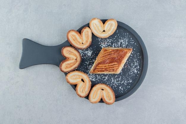 Une planche en bois foncé avec des biscuits en forme de coeur doux.