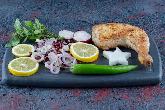 Une planche en bois foncé de légumes et de viande de cuisse de poulet