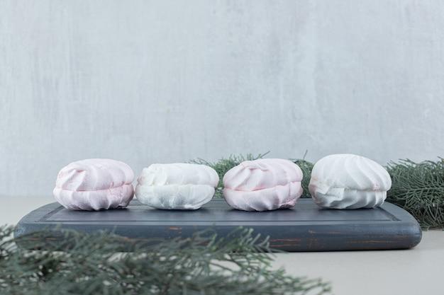 Une planche en bois foncé avec des zéphyrs vanille et rose.