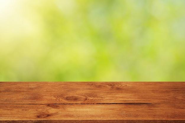 Planche de bois avec fond de feuilles vertes floues