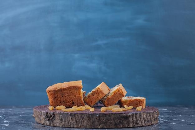 Planche de bois de gâteaux aux raisins secs tranchés sur une surface en marbre.
