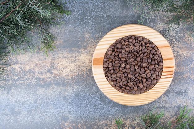 Une planche de bois avec des grains de café sur du marbre