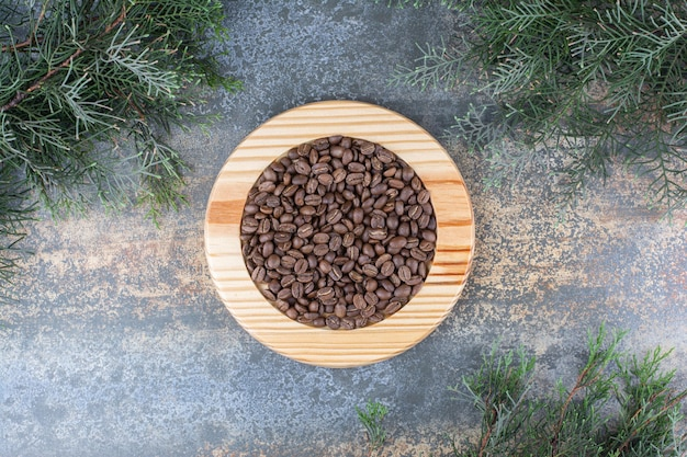 Une planche de bois avec des grains de café sur fond de marbre. photo de haute qualité
