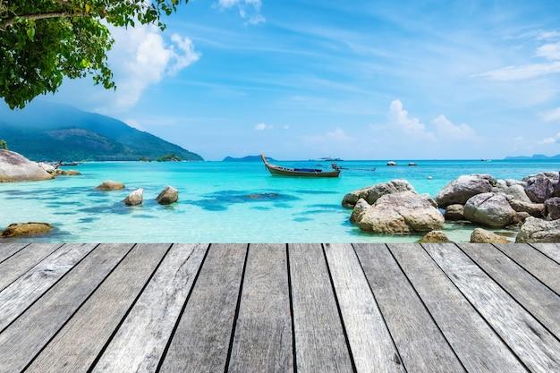 Planche de bois gris sur une mer de cristal avec un bateau à longue queue