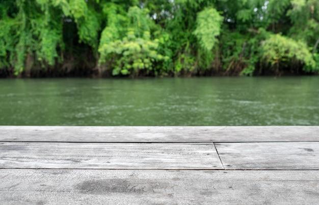Planche de bois grise sur jungle verte floue à la rivière sai yok kwai