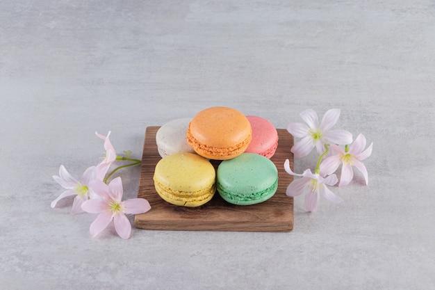 Planche de bois de macarons sucrés colorés avec des fleurs sur la surface de la pierre