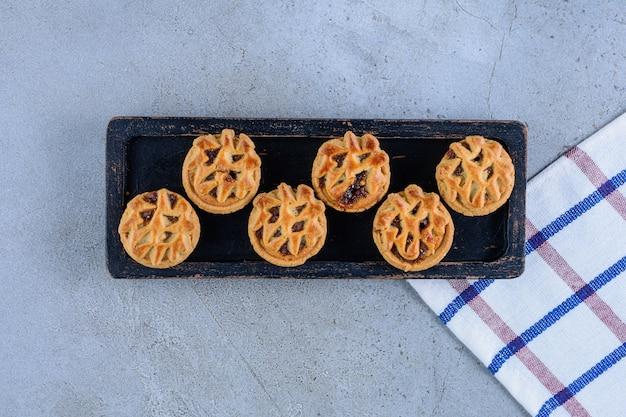 Une planche en bois noir de biscuits aux fruits ronds sur une surface en pierre