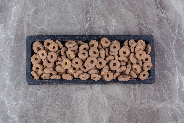 Une planche en bois noire d'anneaux de céréales au chocolat sain pour le petit-déjeuner.
