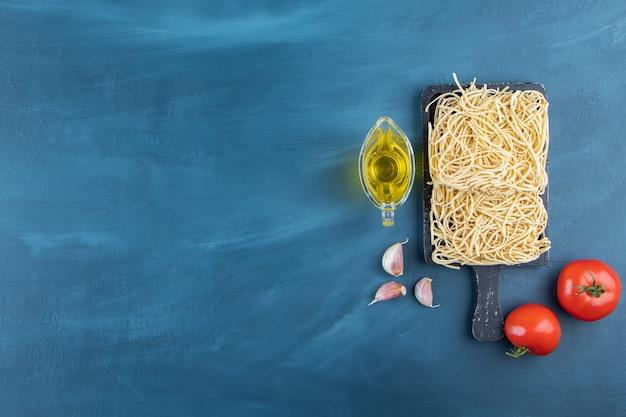 Une planche en bois noire de nouilles crues avec deux tomates rouges fraîches et de l'huile sur fond bleu.