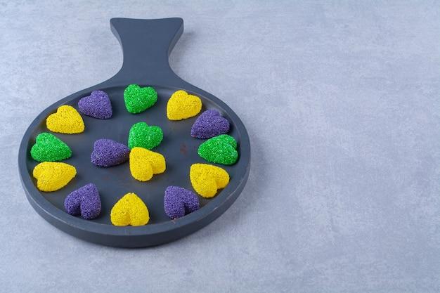Une planche en bois noire pleine de bonbons colorés sucrés.