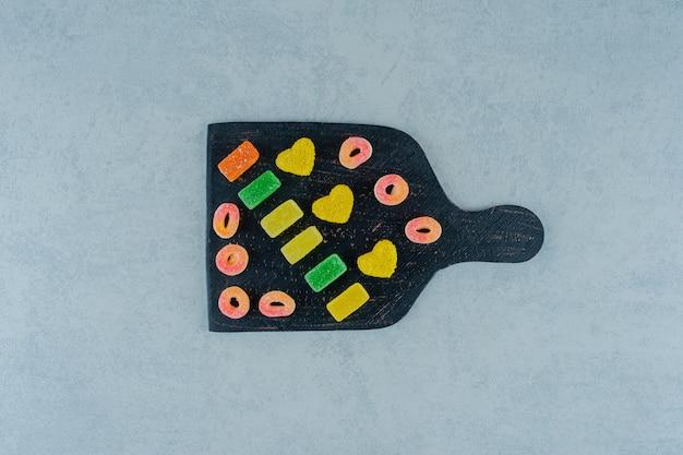 Une planche en bois noire pleine de bonbons à la gelée de fruits colorés sur une surface blanche