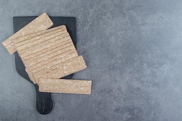 Une planche en bois noire pleine de grahams de pain croustillant.