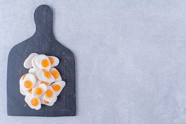 Une planche en bois noire pleine d'œufs frits en gelée sucrée sur une surface grise