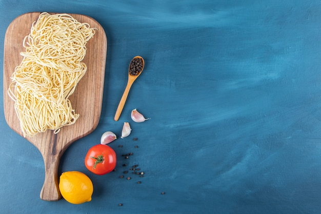 Une planche en bois de nouilles crues avec des tomates rouges fraîches et du citron sur fond bleu.