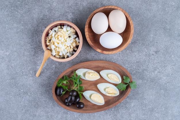 Une planche de bois avec des olives et des œufs durs. photo de haute qualité