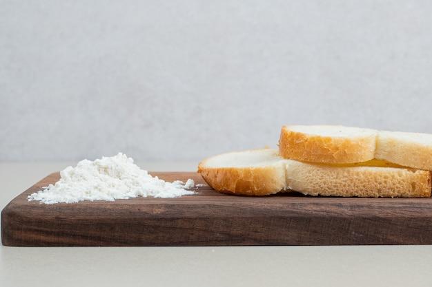 Une planche en bois de pain blanc frais tranché avec de la farine