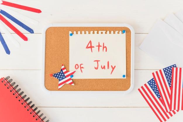Planche de bois avec papier avec texte 4 juillet