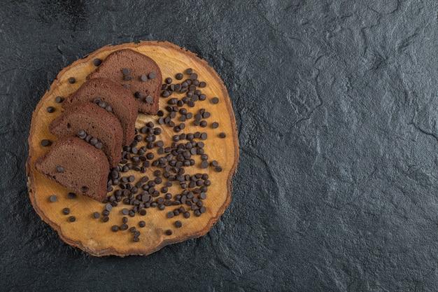 Une planche en bois de pépites de chocolat et de tranches de pain.