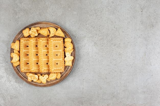 Une planche de bois pleine de biscuits sur fond de marbre.