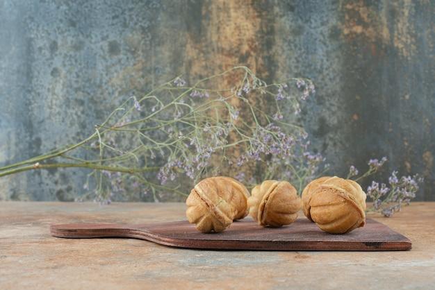 Une planche de bois pleine de biscuits sucrés sur fond de marbre