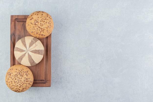 Une planche en bois pleine de biscuits sucrés.