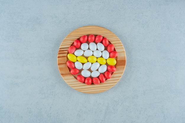 Une planche de bois pleine de bonbons colorés sucrés ronds sur fond blanc. photo de haute qualité