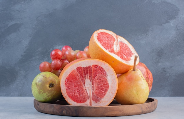 Planche de bois pleine de fruits de saison et de pamplemousse coupé à moitié.