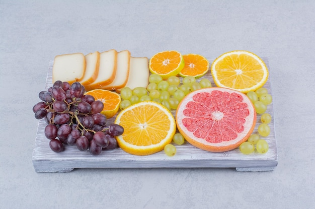 Une planche en bois pleine de fruits tranchés et de pain . photo de haute qualité