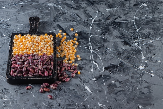 Planche de bois pleine de grains et haricots crus sur fond de marbre.