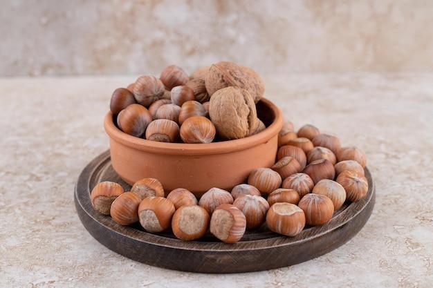 Une planche de bois pleine de noix de macadamia saines.