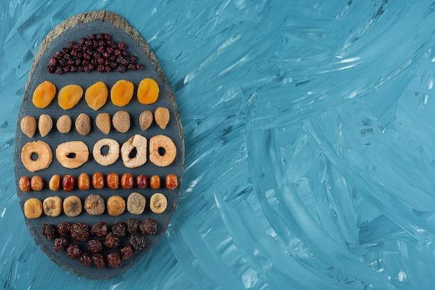 Planche de bois pleine de savoureux fruits secs sur une surface bleue.