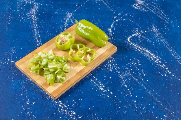 Planche de bois de poivrons verts tranchés sur une surface en marbre.