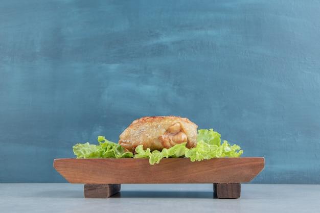 Une planche de bois de poulet frit avec de la laitue .