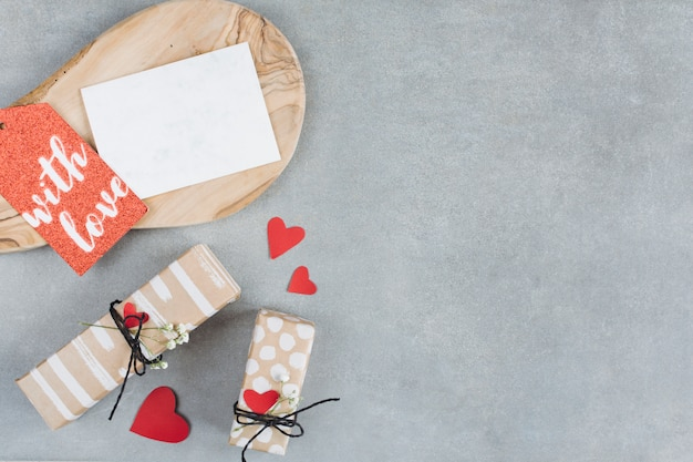 Planche de bois près d'étiquettes, de papier et de boîtes à cadeaux