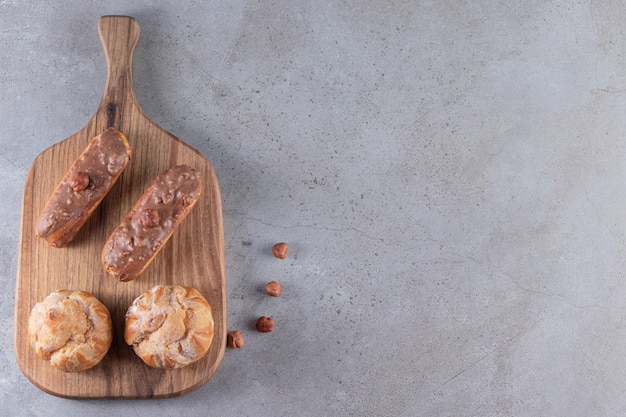 Planche de bois de profiteroles sucrées et éclairs sur table en pierre.
