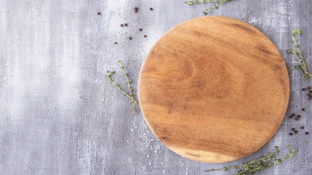 Planche de bois ronde vide avec des épices et des herbes. vue de dessus, espace de texte