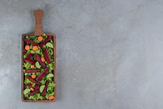 Une planche de bois avec salade de légumes sur fond gris. photo de haute qualité