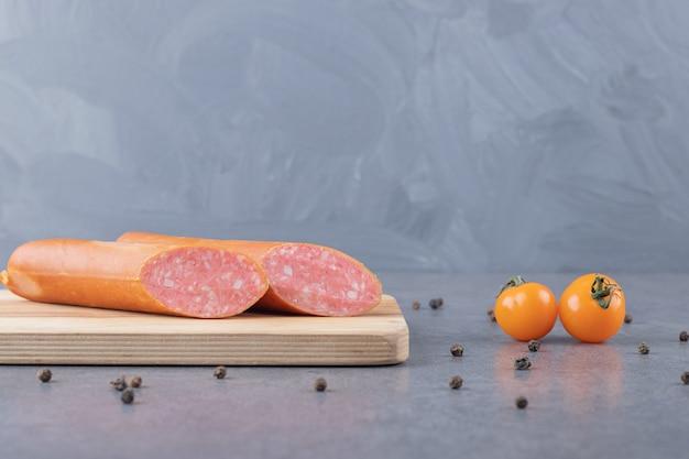 Une planche en bois de saucisses bouillies avec des tomates jaunes cerises