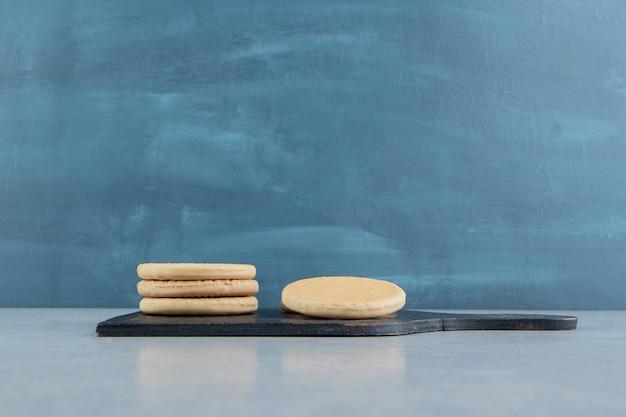 Une planche en bois sombre avec des biscuits ronds sucrés.