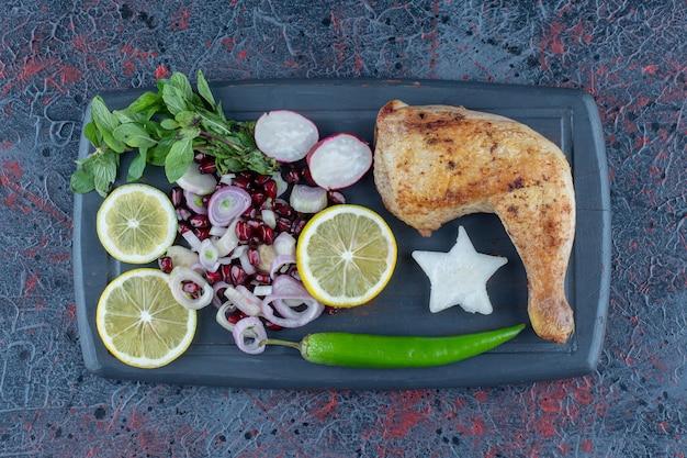 Une planche en bois sombre de légumes et de viande de cuisse de poulet.