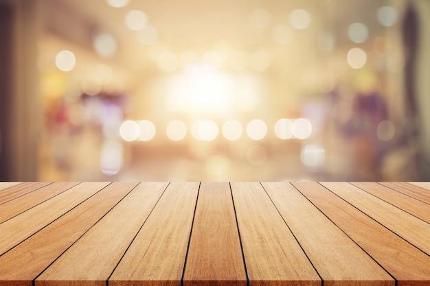 Planche de bois ou une table et l'arrière-plan flou abstrait. l'espace libre peut être utilisé pour le montage photo ou la conception d'affichage de produit et la publicité