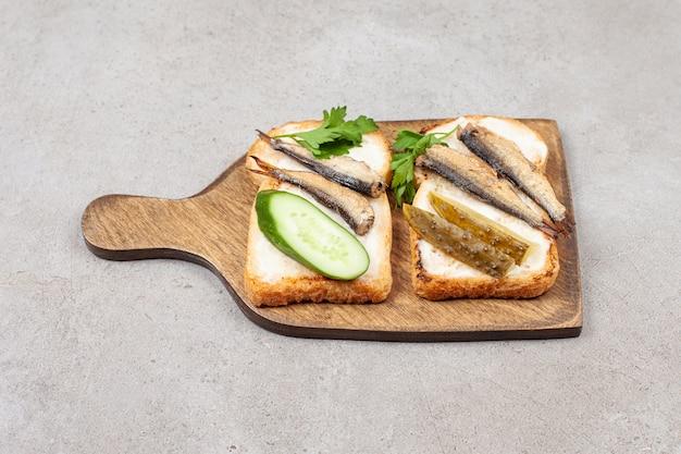 Une planche de bois avec des toasts frits et des sprats