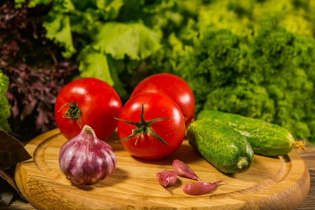 Une planche de bois avec des tomates fraîches, de l'ail et des concombres.
