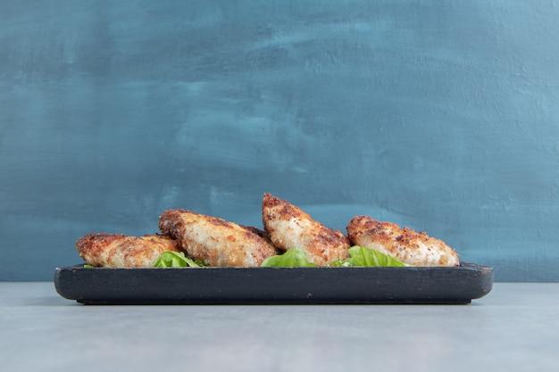 Une planche en bois de viande frite de poulet avec de la laitue.