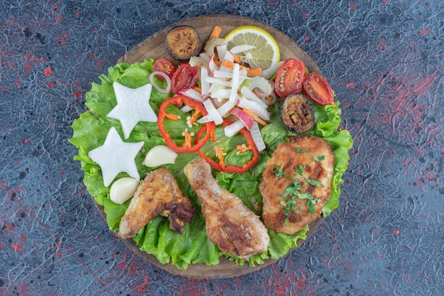 Une planche de bois avec de la viande de poulet et des légumes au four.