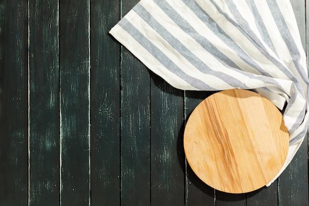 Planche de bois vide avec nappe sur un bureau sombre