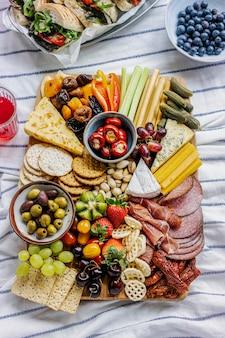 Planche de charcuterie avec de la charcuterie, des fruits frais et du fromage sur une nappe de pique-nique