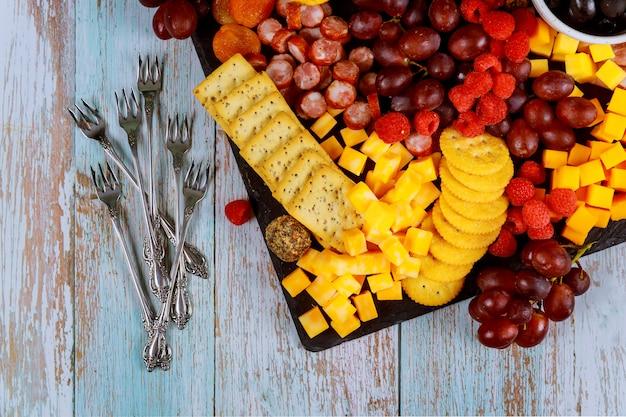 Planche de charcuterie avec cube de fromage, prosciutto, raisins, craquelins et abricots