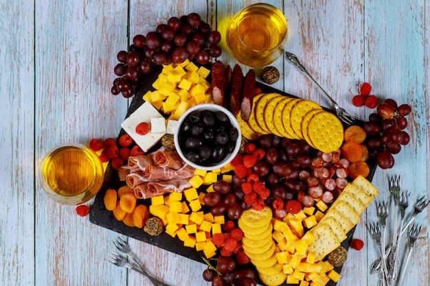 Planche de charcuterie avec fromage, olives, fruits, prosciutto et vin sur table en bois