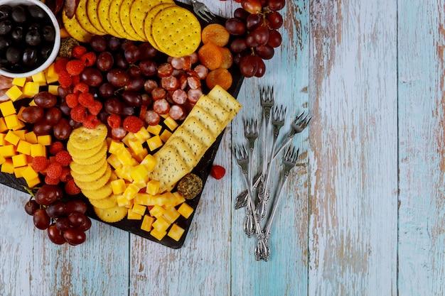 Planche de charcuterie avec fromage, raisin, framboise et craquelins